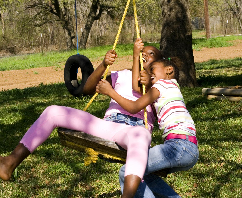Two kids on a swing